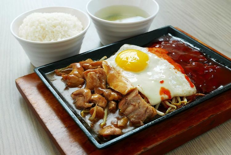 Food served on plate with rice and drink on table indoors