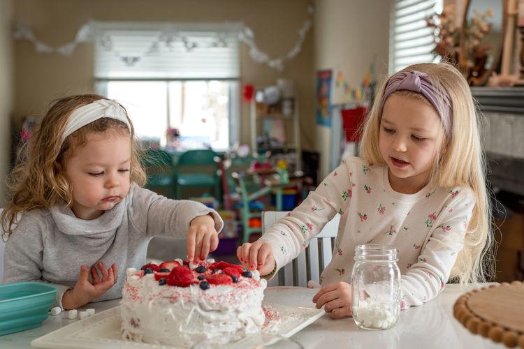 Cute girls eating birthday cake at home