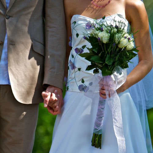 Midsection of bride and bridegroom holding hands during wedding