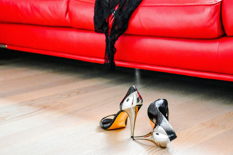 Low angle view of highheels infront of red couch