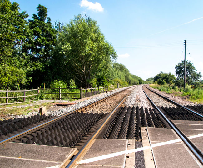 Railroad tracks against sky on sunny day