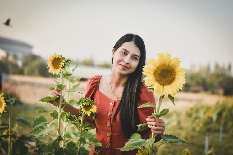 Portrait of smiling young woman with sunflower standing against plants