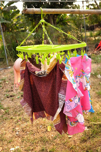 Midsection of woman holding umbrella hanging in back yard