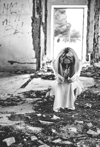 Woman with head in hands crouching in abandoned house