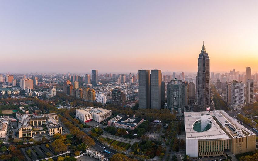 Aerial view of buildings in city at sunset