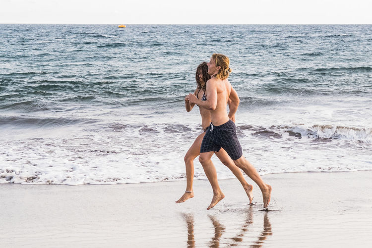 Full Length Of Couple Running At Beach