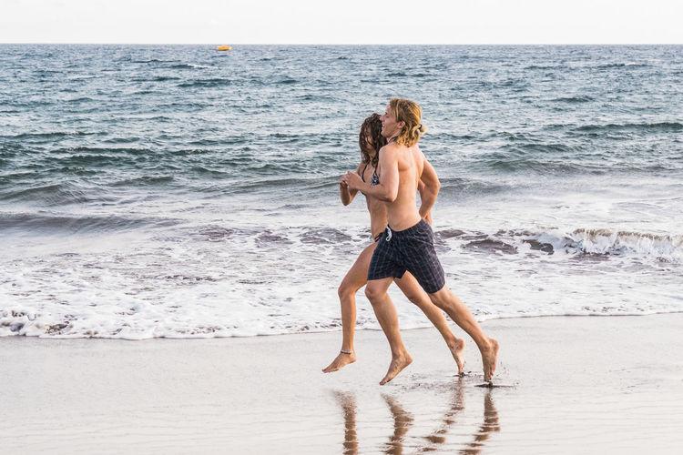 Full length of couple running at beach