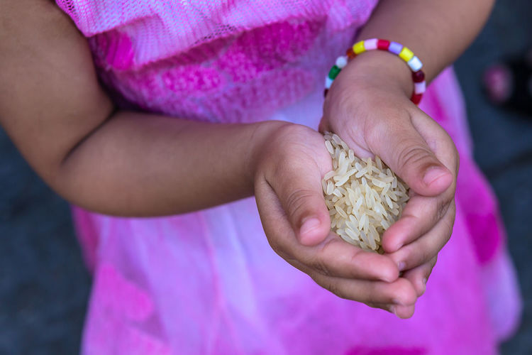 Close-Up Of Girl Holding Rice