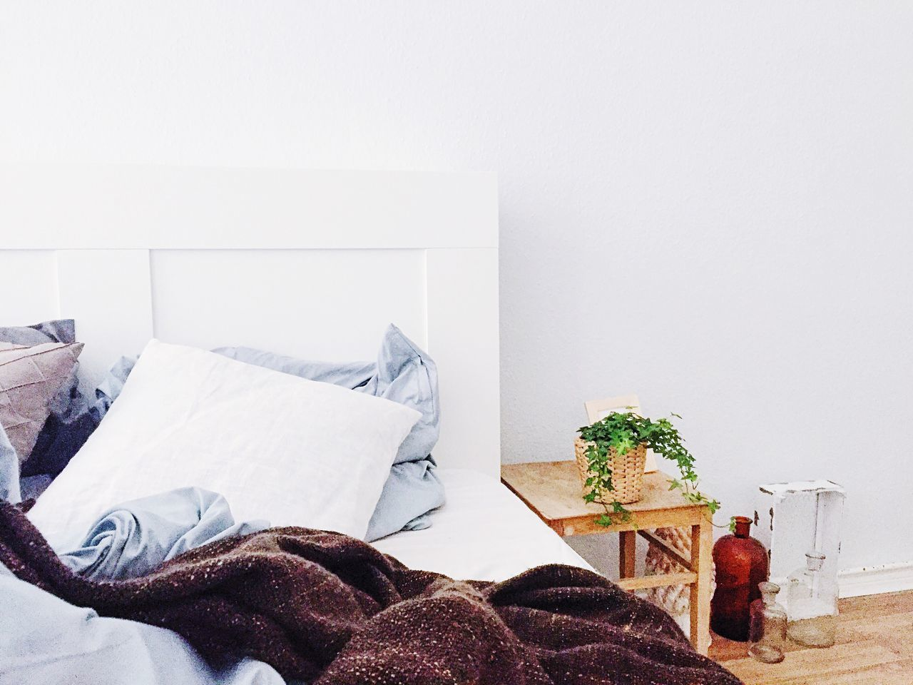 Crumpled blanket on bed by potted plant on table in bedroom