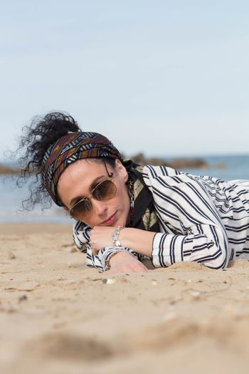Portrait of woman in sunglasses lying at beach