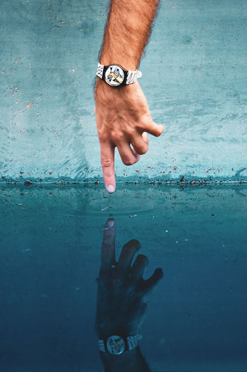 Ying Yang Pool Time Water Reflections Winter Adult Body Part Bracelet Cold Temperature Day Finger Hand Human Body Part Human Finger Human Hand Human Limb Leisure Activity Lifestyles Low Section Men One Person Pointing Pool Real People Reflection Touching Water Be Brave