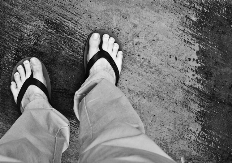 Low Section Of Person Wearing Flip-Flop Standing On Wet Footpath