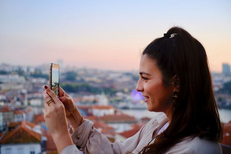 Portrait of young woman using smart phone against sky during sunset