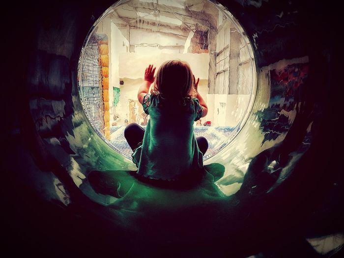 Rear view of girl sitting in slide