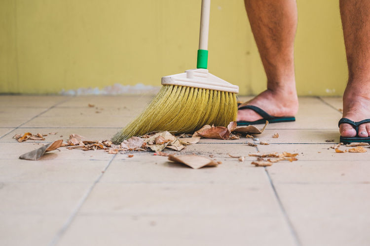 Low section of man cleaning floor with broom