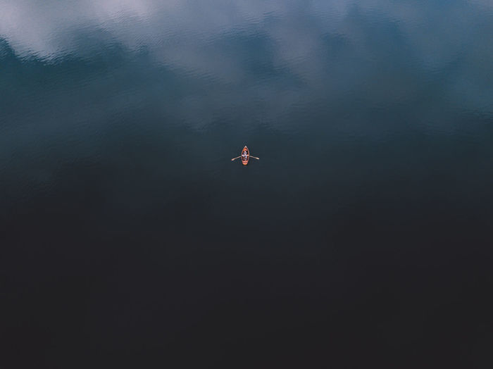 Top view of a orange boat sailing in the dark blue water. view of row boat wih human hands paddling