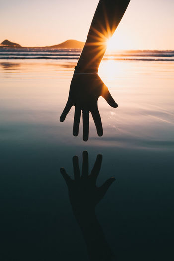 Beauty In Nature Body Part Finger Hand Human Body Part Human Hand Leisure Activity Lens Flare Lifestyles Nature One Person Orange Color Outdoors Real People Reflection Scenics - Nature Silhouette Sky Sun Sunlight Sunset Water 10