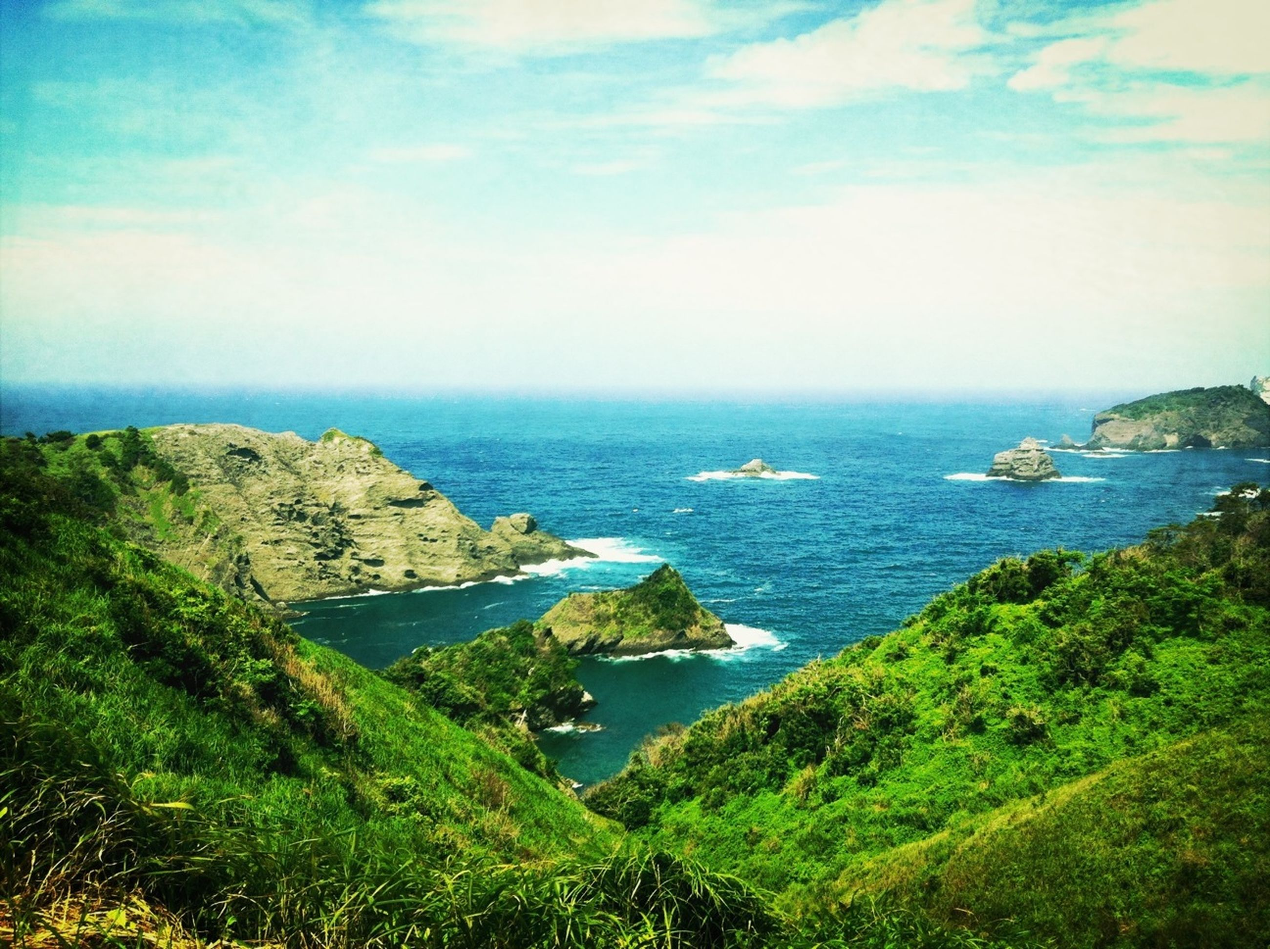 sea, water, horizon over water, tranquil scene, scenics, tranquility, beauty in nature, sky, nature, cliff, high angle view, coastline, rock formation, rock - object, idyllic, blue, rock, landscape, non-urban scene, grass