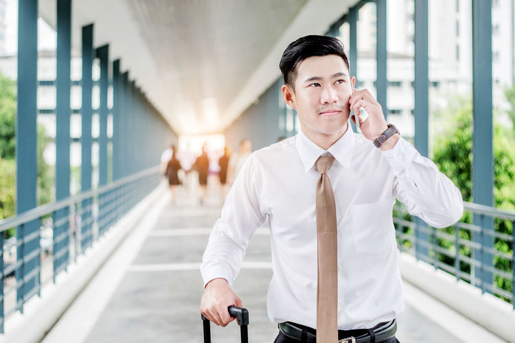 Businessman talking on mobile phone while standing on bridge