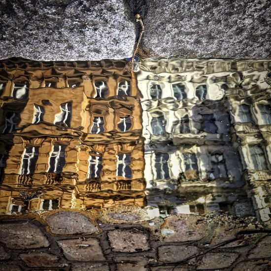 Reflection of building in water puddle on footpath