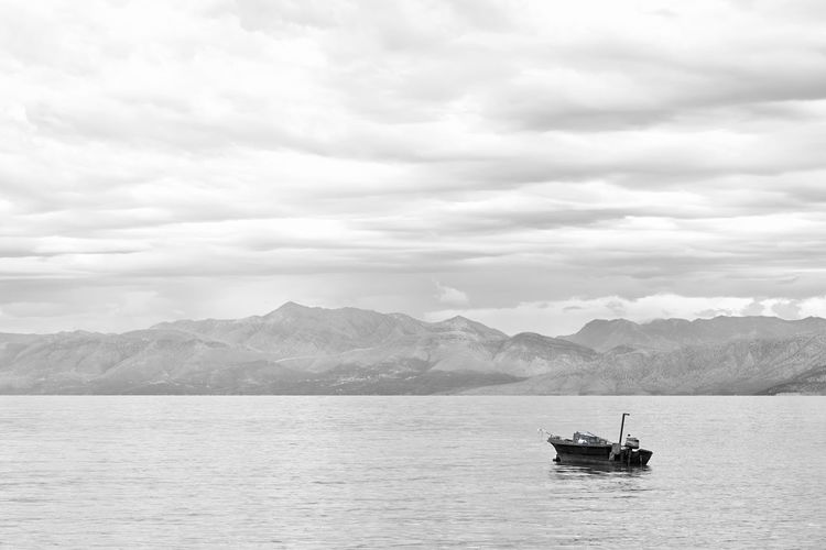 Fishing Boat Sky Water Cloud - Sky Mountain Sea Nature Day Travel Transportation Fishing Boat Greece Overcast Backgrounds Copy Space Ocean Scenics Scenery Beautiful Travel Tourism Black And White Monochrome Tranquility Calm Sea Outdoors