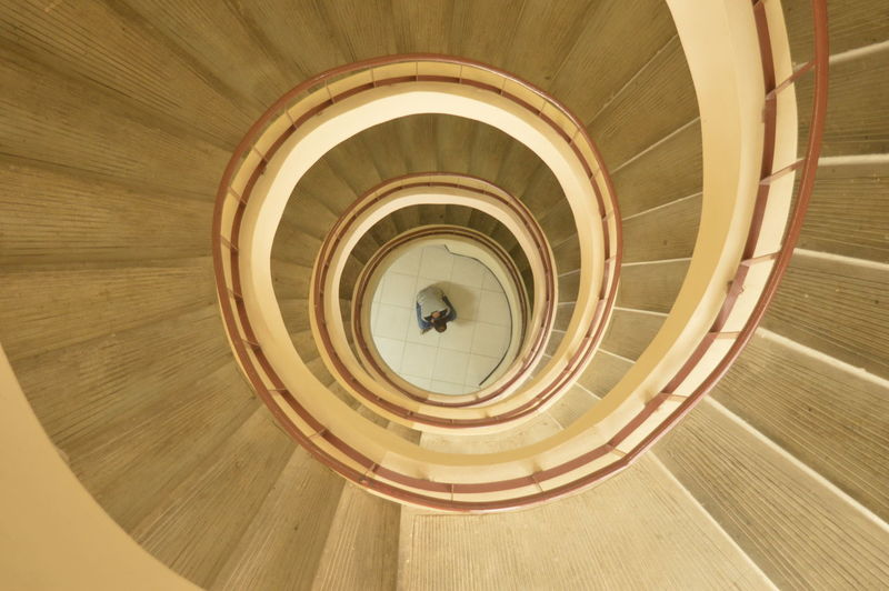 Directly above shot of man by spiral staircase