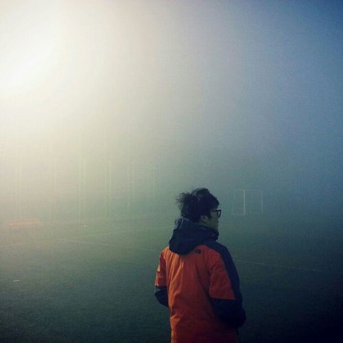 Rear view of man standing in foggy weather