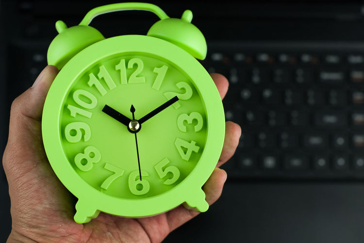 Cropped hand holding green alarm clock at home