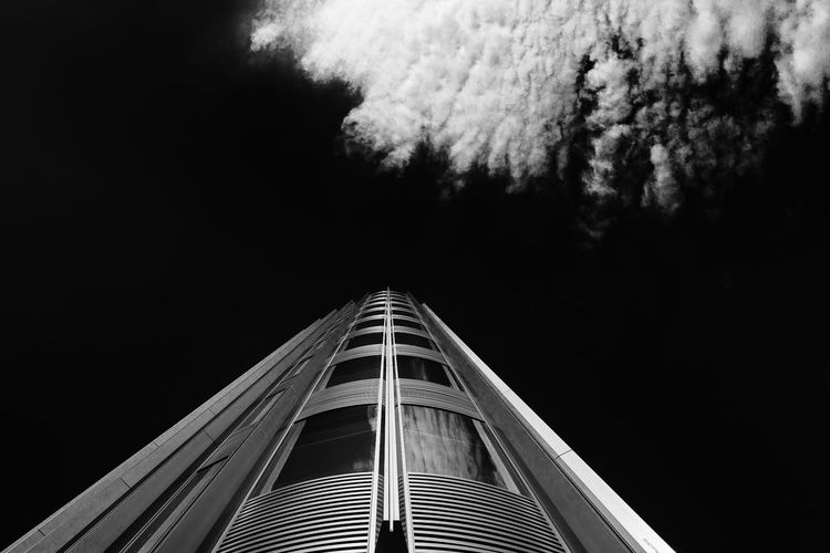 Low-angle view of a modern tower building with metallic frame