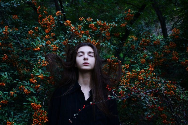 Beautiful Young Woman Standing Against Plants In Forest
