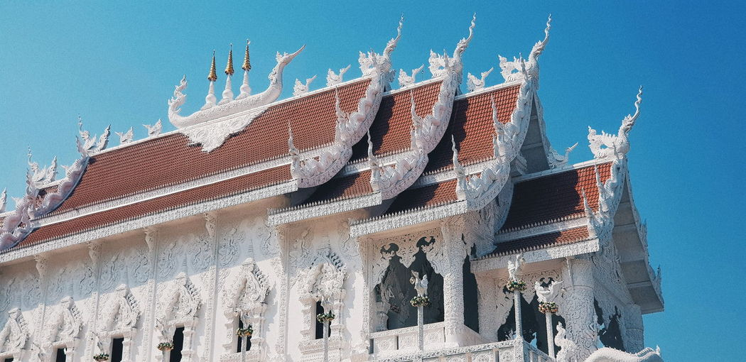 Low angle view of sculptures on building against clear blue sky