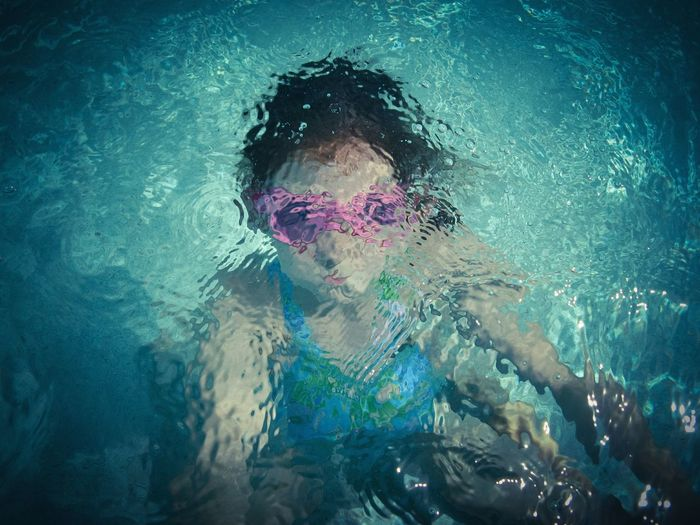 High Angle View Of Girl In Rippled Swimming Pool