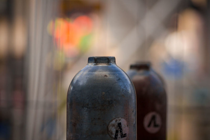 Close-Up Of Gas Cylinders Against Blurred Background