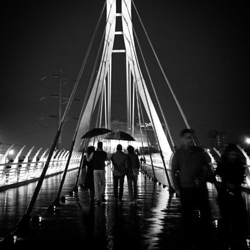 People walking on cable stay bridge at night