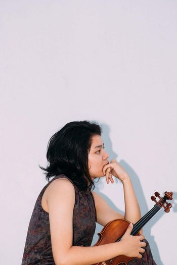 Music Musical Instrument Musician Violin Playing One Person Guitar Arts Culture And Entertainment String Instrument Black Hair White Background Plucking An Instrument Ukelele Violinist Holding Studio Shot Young Adult Leisure Activity Performance