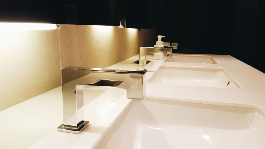 Close-up of faucet with sinks in dark bathroom