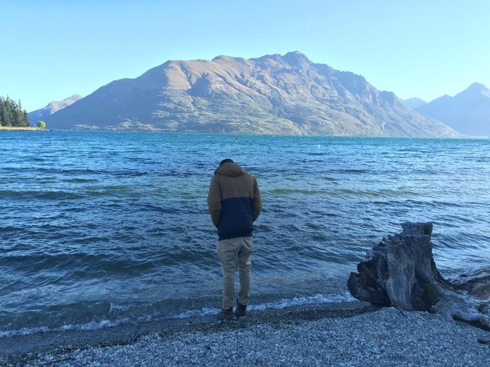 Rear View Of Man Standing On Lakeshore Against Mountain