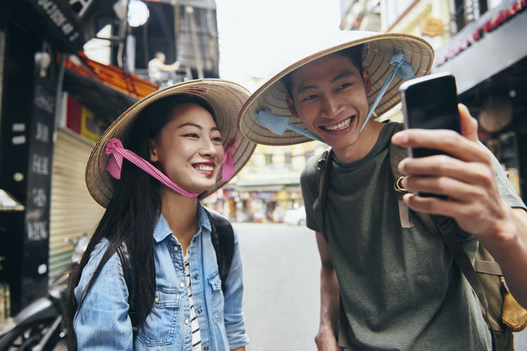 Portrait of smiling young couple wearing hat taking selfie at market