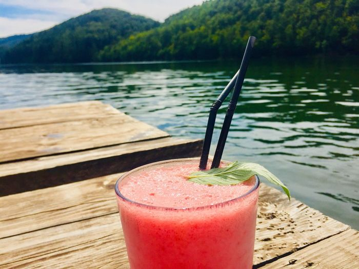 Glass of strawberry lemonade with mint placed on wooden pontoon near the lake