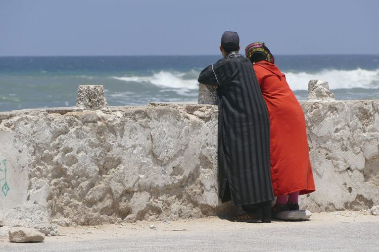 Woman and man in traditional clothing standing on cement jetty