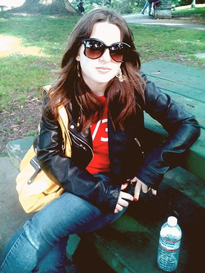 Young woman wearing sunglasses sitting outdoors
