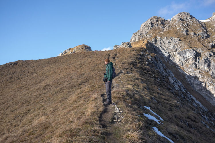 Rear view of man walking on rock against sky