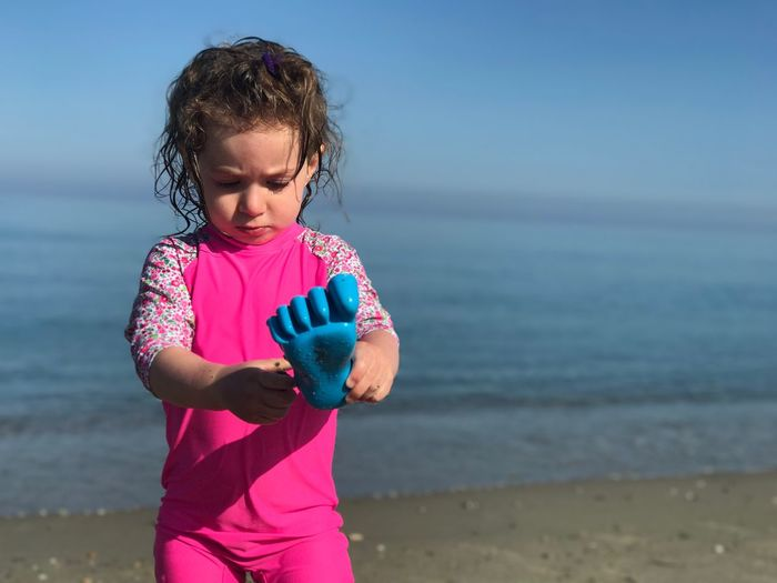Girl Holding Toy While Standing At Beach