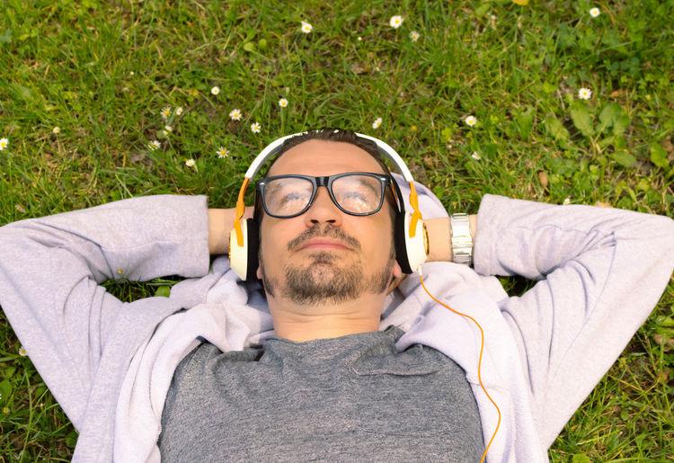 Portrait of man lying down on grass