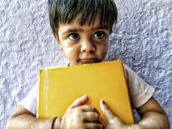 Close-up of baby boy holding book looking away while standing against wall