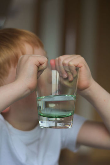 Child Holding A Glass Of Water