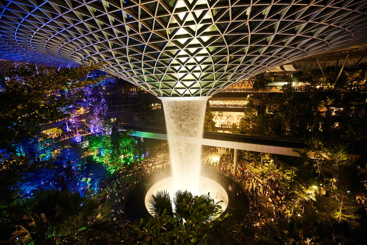 Changi Airport Singapore Jewel Vortex Water Fountain Trees Illuminated Architecture Built Structure Plant Night Tree No People Nature Connection Motion Bridge Outdoors Bridge - Man Made Structure Long Exposure Building Exterior Lens Flare Blurred Motion