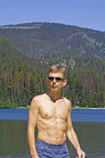 Shirtless Mature Man Wearing Sunglasses While Standing Against Lake And Mountain At E C Manning Provincial Park