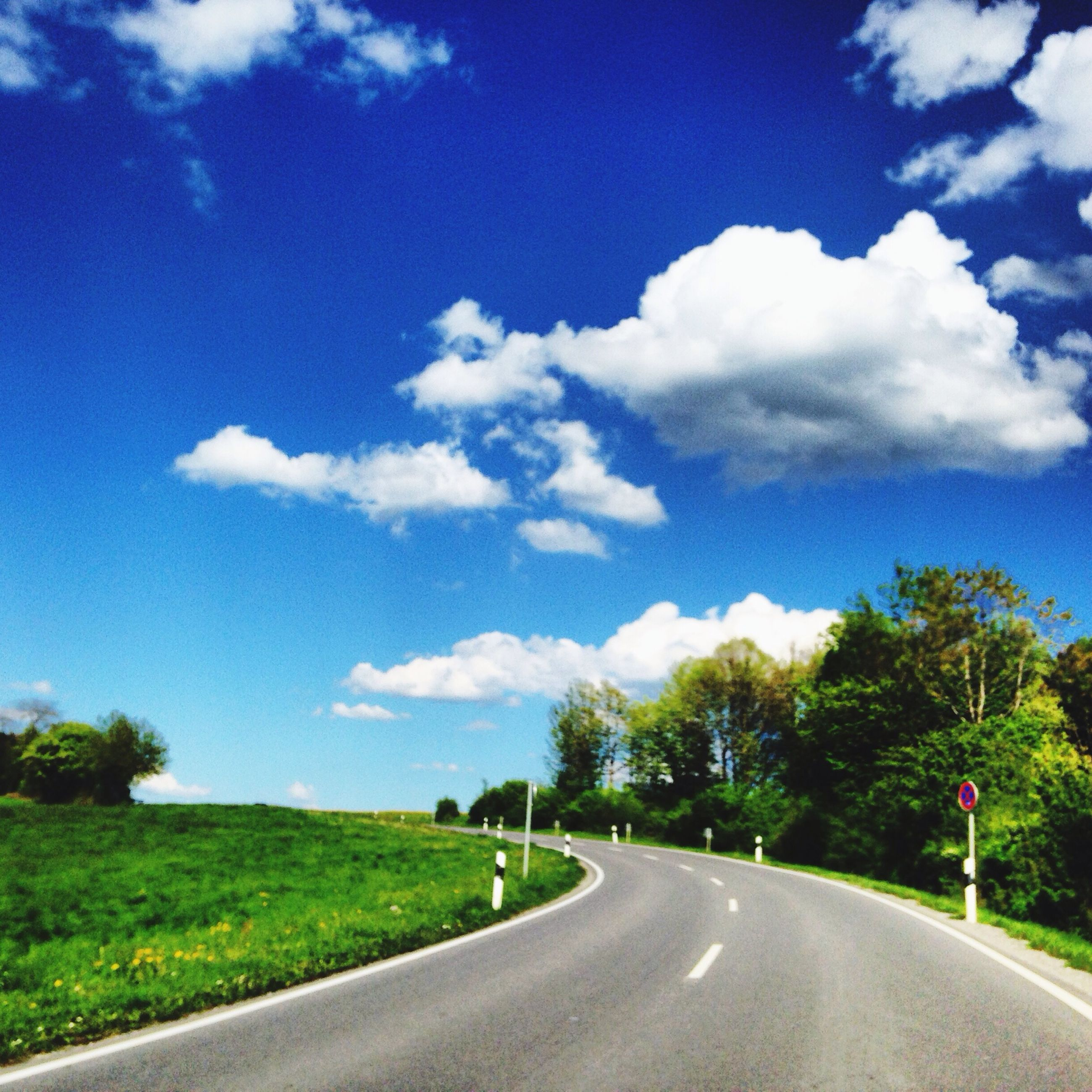the way forward, road, sky, diminishing perspective, tree, transportation, country road, vanishing point, road marking, tranquility, tranquil scene, cloud - sky, cloud, grass, landscape, empty road, blue, empty, nature, long