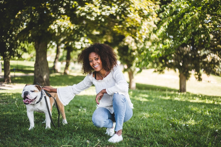 Full length of woman with dog on grass